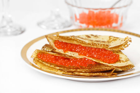 Red caviar and pancakes on a large white plate.