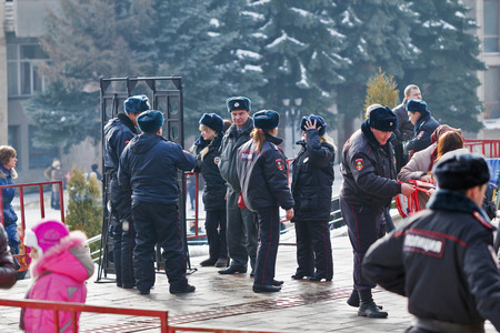 Russia, Pyatigorsk - January 23 - 2014: Police officers inspect personal belongings from frame metal detector in people going on a mass event.