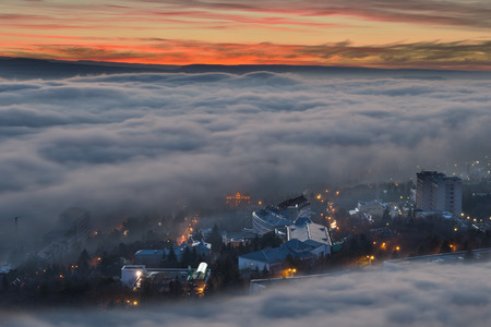 Evening city visible through the mist and clouds  Stock Photo