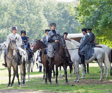 The men in the uniform  the Terek Cossack Army Cossacks on horseback on a background of green trees.  Editorial