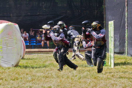 Pyatigorsk, Russia - July 19, 2014: Competitions paintball. Competitions are held on a sunny day in a forest glade equipped for such competitions. Team of athletes dressed in protective uniforms leads shooting from airguns.  Editorial
