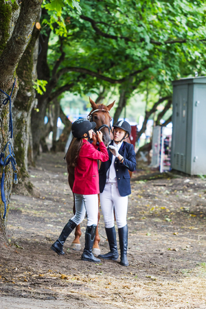 Pyatigorsk. Russia - September 11, 2014: Pyatigorsk. Glade in the Forest.Girls holding a horse by the bridle.  Editorial