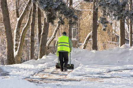 Worker in bright green uniforms removes snow in the city park.