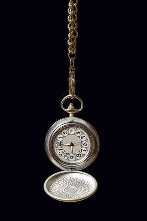 Old pocket watch hanging on a chain. Dark background.