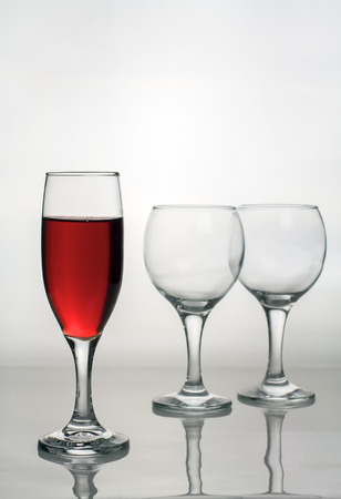 Empty  stemware and wine glass with red wine.