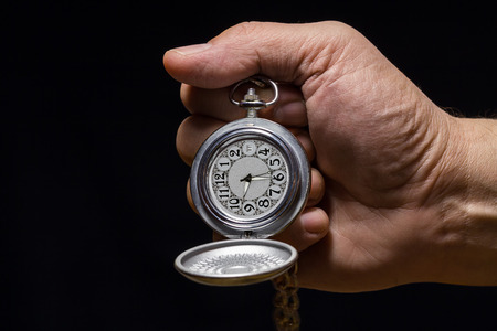 Pocket watch with chain silvery color in the mens hand.