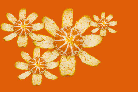 Oranges peel with slicings in the form of a flower on orange background. Stock Photo