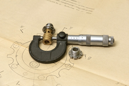 micrometer: Measuring tools (micrometer) and metal details lying in the drawing. Stock Photo