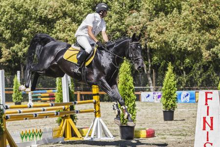 pyatigorsk: Pyatigorsk. Russia - September 05.09.2015 : Pyatigorsk. Demonstration performances. The rider on the black horses jumps an obstacle.