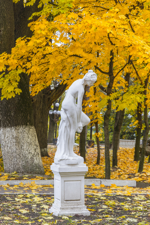 A marble sculpture of a woman in  autumn park. Stock Photo