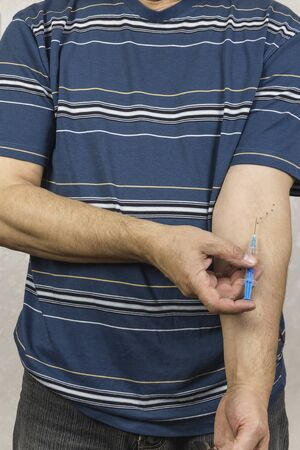 A drug addict injects in hand with traces of injections.