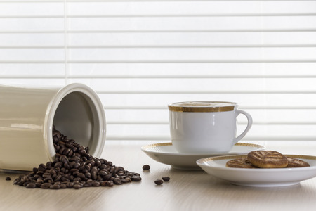 frijol: Taza de caf� y granos de caf� esparcidos sobre la mesa.