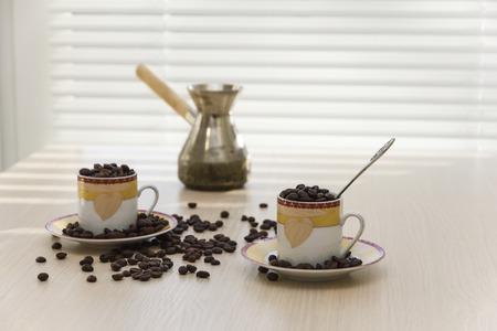 Tazze di caffè, macchina da caffè e chicchi di caffè sul tavolo.