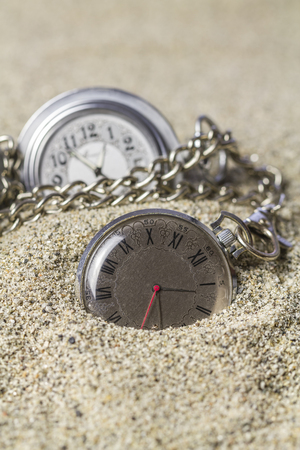 Pocket watch with its Roman and by Arabic numerals lie on the sand.