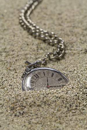 sand watch: Gold pocket watch with chain covered with sand.
