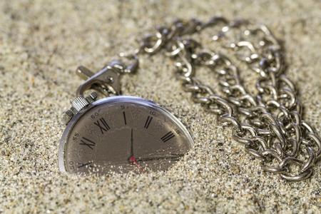 numeros romanos: Antiguo reloj con números romanos y una gruesa cadena de mentira en la arena.