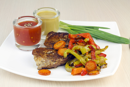 Steak with roasted vegetables, fresh onion and sauce on a plate.