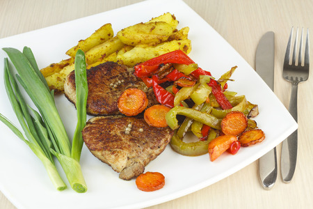 Steak with roasted vegetables, fresh onions and potatoes. Stock Photo