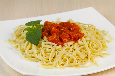 Spaghetti with tomato sauce on a white plate.