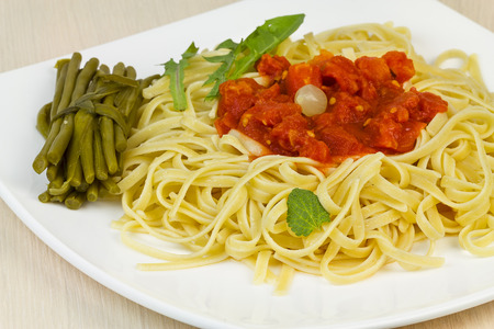 Spaghetti with sauce, salad leaves and posies of pickled beans. Stock Photo