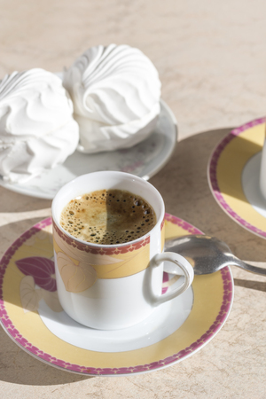 Black coffee with thick foam and marshmallow on a platter. Stock Photo
