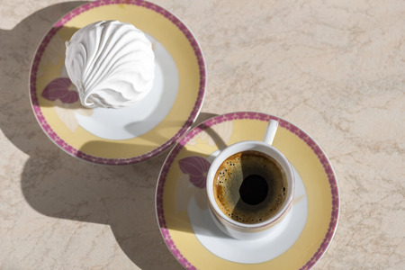 A cup of black coffee and cake in a saucer.