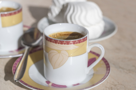 A cup of coffee with crema, spoon and cake. Stock Photo