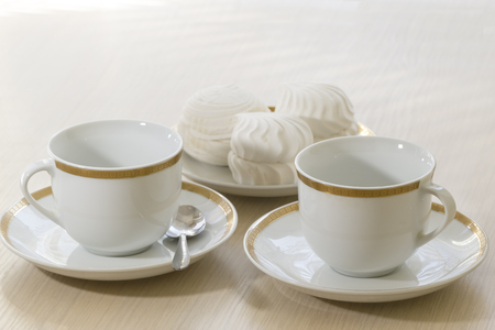 Two white coffee cups cake on the table.