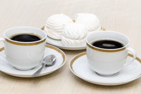 Two large white cups with black coffee and dessert.