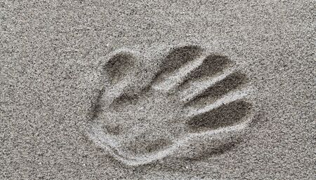 The imprint of a mans hand on the sand. Stock Photo
