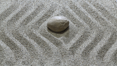 Stones and flowing wavy lines on the sand.