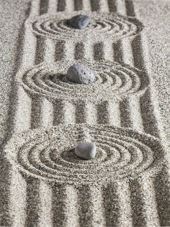 Stones, circles and lines on the sand.