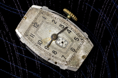 Old wrist watch close up on a dark background.