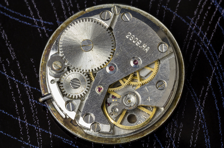 The mechanism of old wristwatches closeup on a dark background.