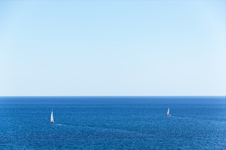 Two yachts under the white sails on a background of blue sea water.