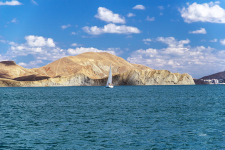 The yacht floating on the blue sea water against a rocky shore