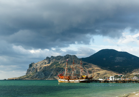 Pleasure craft stylized sailing ship at the pier in the background of the mountain Karadag.