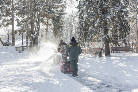 Workers are clearing the snow from the city park using a machine for snow removal. Stock Photo