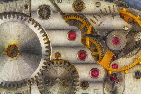 Old rusty clockwork with ruby stones and rusty gears. Stock Photo