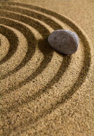 Grey stone lies on the undulating sandy surface.