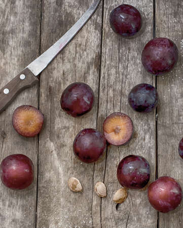 Ripe plums on a wooden background