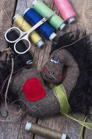 ミシン アクセサリーの背景に自家製の柔らかいおもちゃの馬 写真素材