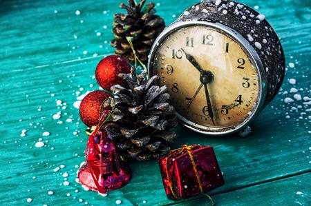 青緑色の木製の背景上のクリスマスの装飾と古い時計