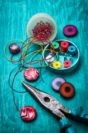 coil,beads and tools for needlework on turquoise wooden background Stock Photo