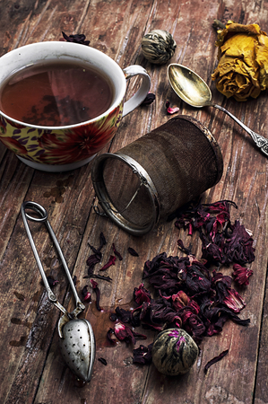 tea strainer and different varieties of tea leaves on wooden background.The toned image