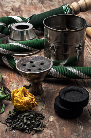 dismantled: details Shisha and accessories on wooden background.image is tinted in vintage style