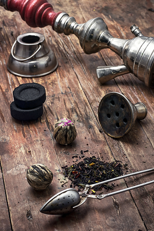 crack pipe: accessories to Smoking hookah and dry tea leaves.image is tinted in vintage style