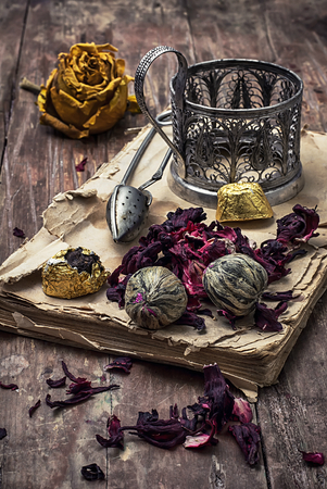 tinted: old book is strewn with the tea leaves on wooden background,tinted in vintage style Stock Photo