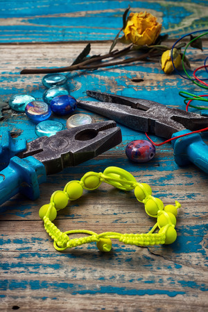 beads,pliers,and other needlework accessories on outdated turquoise wooden background