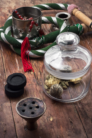 crack pipe: accessories to smoking hookah and dry tea leaves. Stock Photo